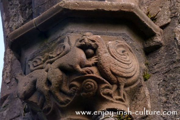 Abbey at Boyle, County Roscommon, Ireland, decorative medieval stone carvings of peacock and wild cats fighting over ahuman head.