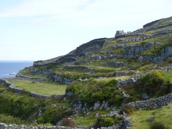 Inisheer landscape, County Galway, Ireland with the ruin of the medieval O'Flaherty castle on top of the hill.