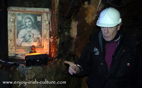 Michael the guide Mining Museum pointing at the sacred heart lamp as he talks about the importance of religion to this close knit mining community.