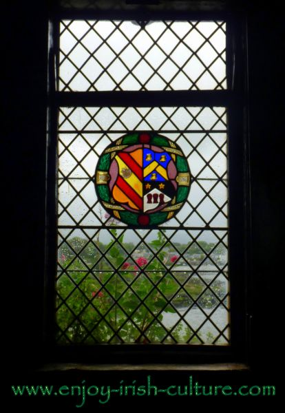 View out the window of the castle revealing a heraldic crest of the medieval owners.