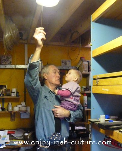 Irish piper and instrument maker Eugene Lambe switching off the light in his workshop after a days' work is done.