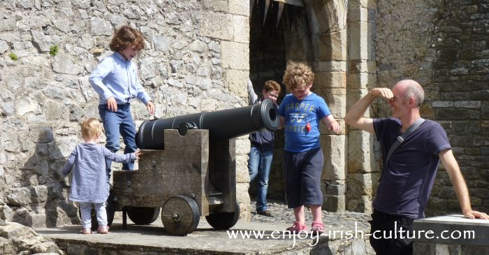 Kids of all ages having fun with a cannon at Cahir Castle, County Tipperary, Ireland.