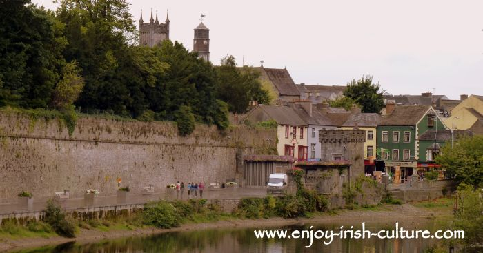 Walk along the river Nore following the curtain wall of the castle, with a view of the town of Kilkenny, Ireland.